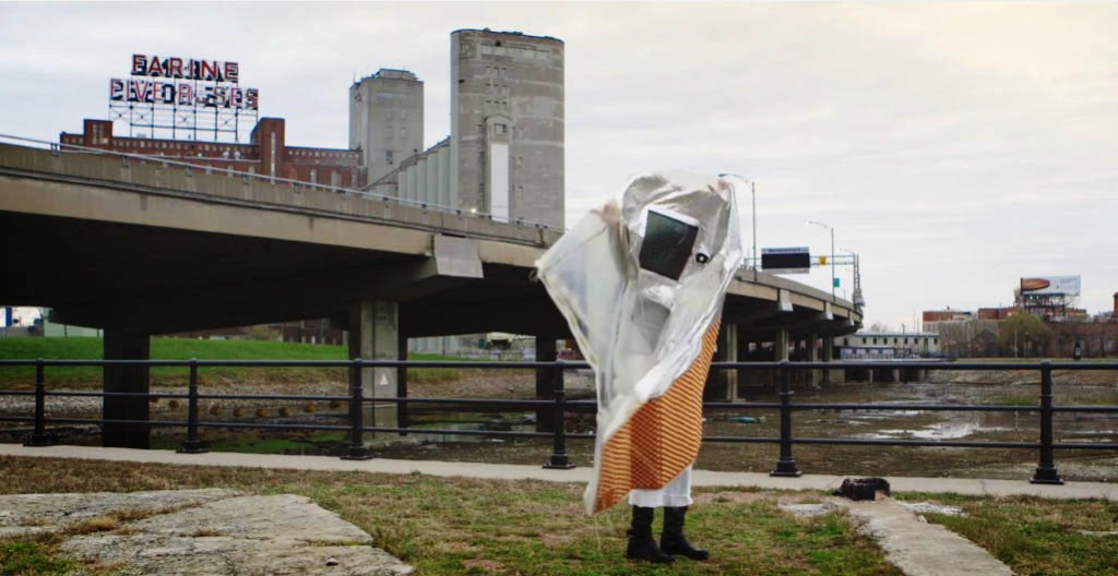 Montreal artist Ana Rewakowicz arranges her Sleeping Bag Dress, in the documentary film Microtopia. Note the Farine Five Roses sign in the background.