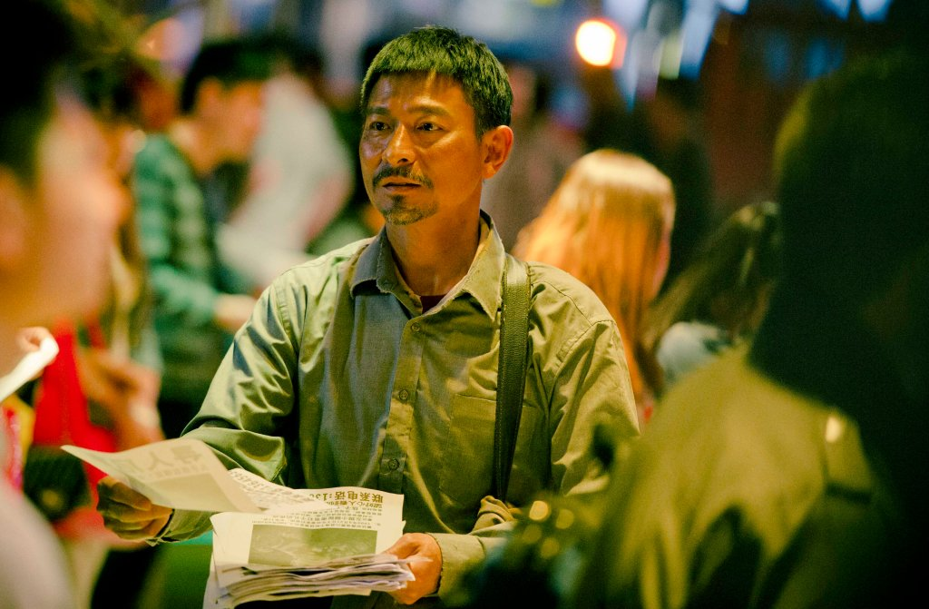 Lei Zekuan (Andy Lau) passes out fliers with photos of his missing son in a scene from the Chinese film Lost and Love. (China Lion Film Distribution)