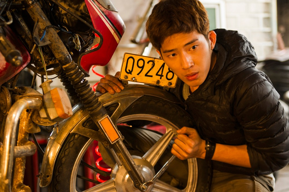 Zeng Shuai (Jing Boran)  repairs Lei Zekuan's damaged motorcycle in a scene from the Chinese film Lost and Love. (China Lion Film Distribution)