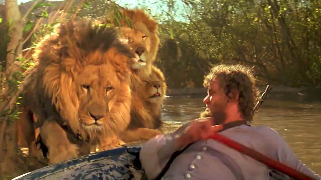"""Hey, wait for us!"" Hank (Noel Marshall) thinks that he's going somewhere in that boat, but the lions have another idea, in a scene from the 1981 film Roar."