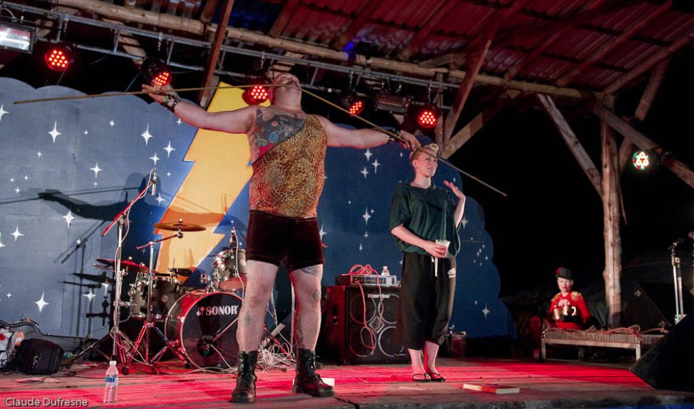 Strongman The Mighty Leviticus, of The Blue Mushroom Sirkus Psyshow performs at an earlier edition of ShazamFest. I do believe that he is bending steel rebar with his teeth. (Does his dentist know about this?  Photo, by Claude Dufresne, from ShazamFest web site.