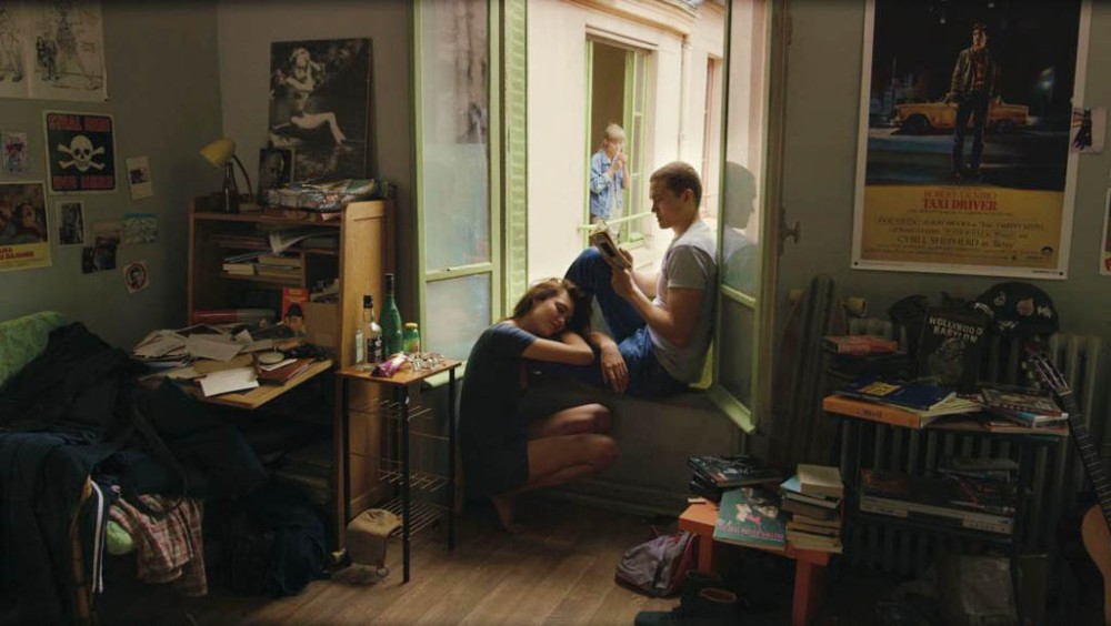 In this scene from Gaspar Noe's film Love, Electra (Aomi Muyock) and her boyfriend Murphy (Karl Glusman) relax in their Paris apartment. New neighbour Omi (Klara Kristin) can be seen through the window.