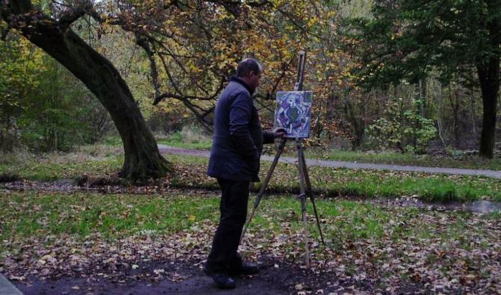 A man paints in nature, though not from nature, in a scene from the French documentary film The Woods Dreams Are Made Of (Le Bois Dont Les Rves Sont Faits).