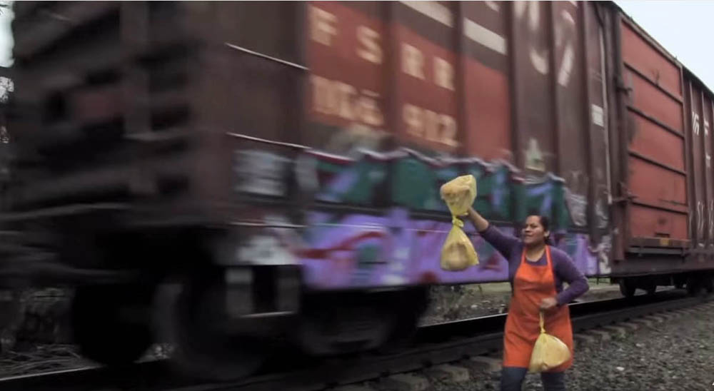 In a scene from the film LlŽevate mis amores, a member of the group Las Patronas holds bags of food for Central American migrants travelling north on a freight train.