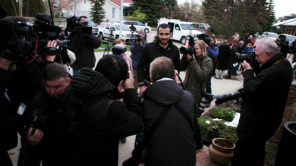 Omar Khadr, centre, talks to members of the media outside the Edmonton home of his lawyer Dennis Edney.