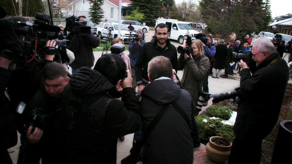 Omar Khadr, centre, talks to members of the media outside the Edmonton home of his lawyer Dennis Edney.