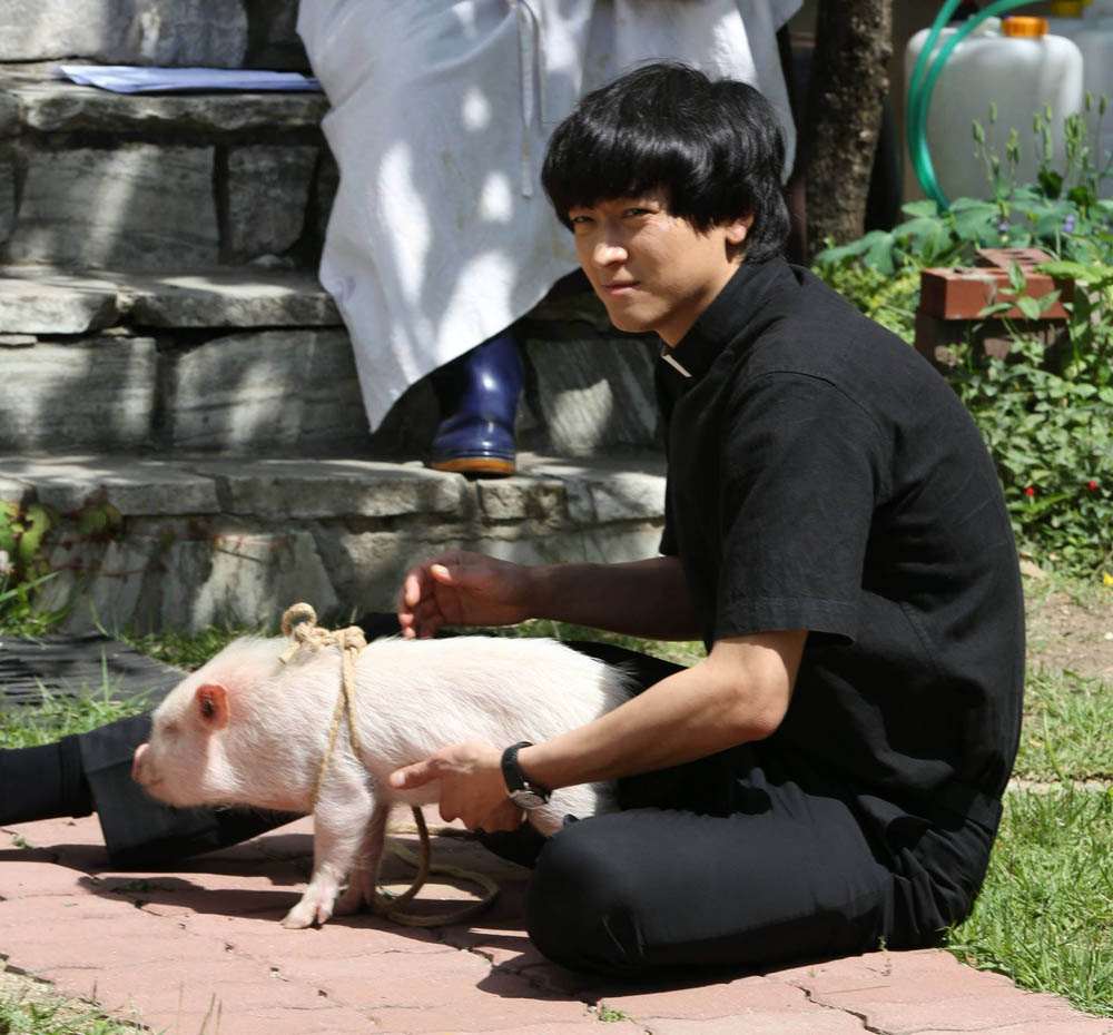 Actor Kang Dong Won and a cute little piglet take a break during the filming of the Korean movie The Priests. (CJ Entertainment photo)