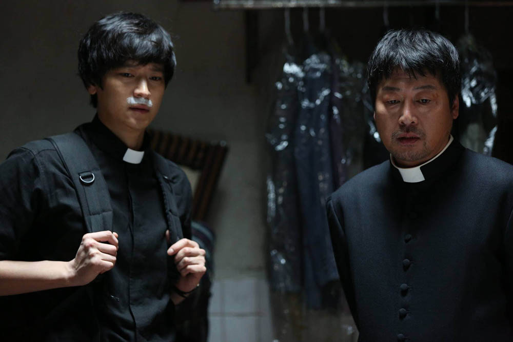 Kang Dong Won,left, and Kim Yun Seok in the Korean film The Priests. What is that, under Kang Dong Won's nose? Not quite a milk moustache. . .is is part of the ritual to oust the demon? (CJ Entertainment photo)
