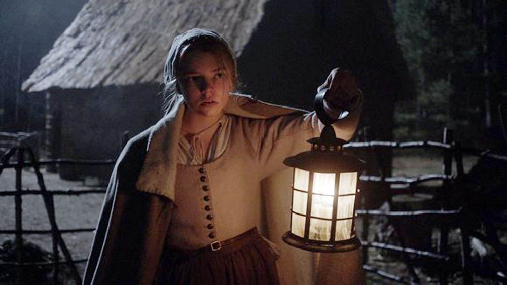 In this scene from the horror film The Witch, Thomasin (Anya Taylor-Joy) has heard disturbing sounds in the night. (Remstar Pictures)