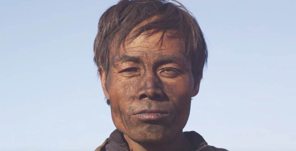 The sooty face of a coal miner in Zhao Liang's documentary film Behemoth.