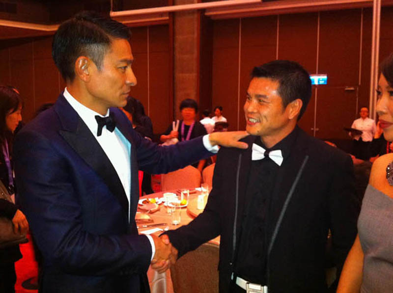 Hong Kong actor Andy Lau, left, shakes hands with Qi Moxiang at the 2012 Golden Horse Awards in Taipei, Taiwan. Qi is the main character in the documentary China Heavyweight, by Canadian director Yung Chang.